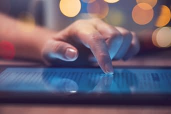 Woman reading online news on digital tablet, close up of hands using device